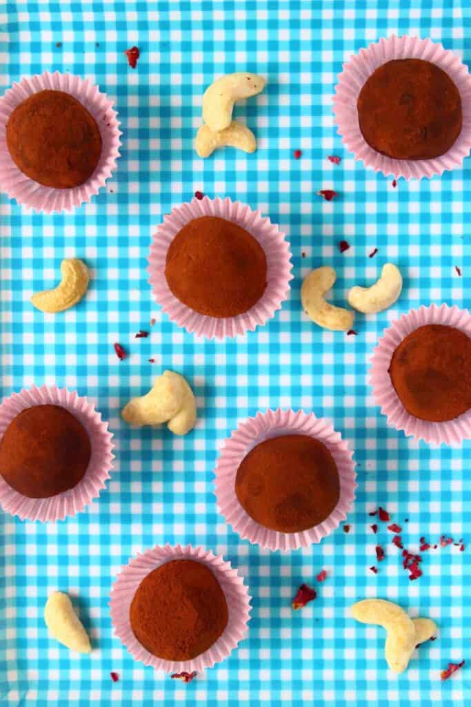 Photo of seven chocolate truffles in pink mini cupcake cases against a blue and white checked background sprinkled with cashew nuts around