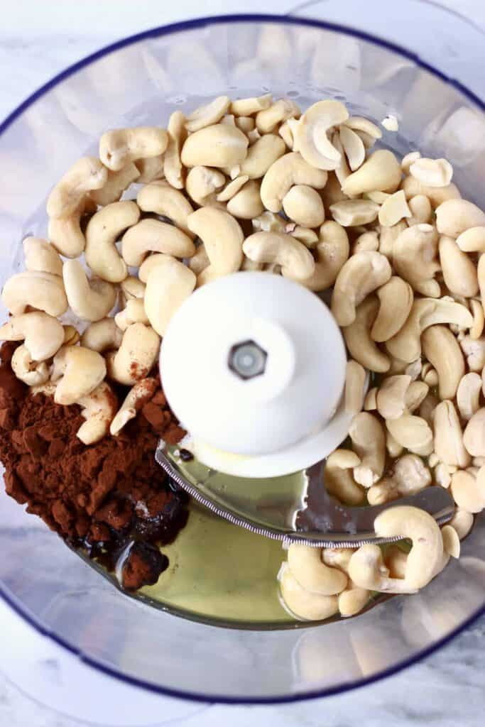 Photo of cashew nuts, cocoa powder, agave syrup and melted cacao butter in a food processor against a marble background