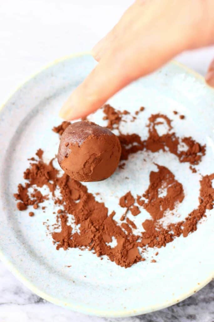 Photo of a chocolate truffle being rolled in cocoa powder on a blue plate with a finger
