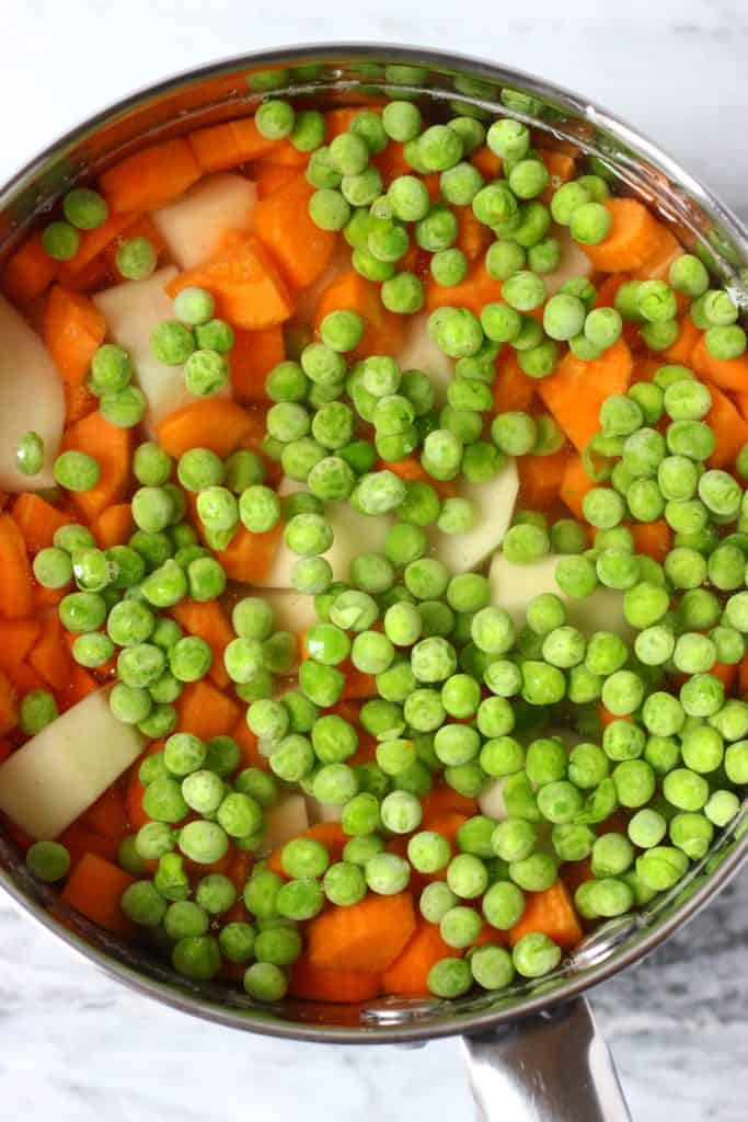 Diced potatoes, carrots and green peas in a silver saucepan filled with water against a marble background