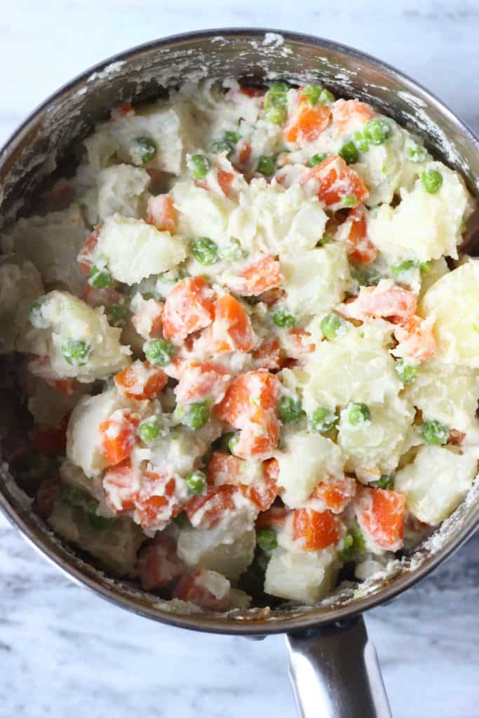 Potato salad with carrots, green peas and mayonnaise in a silver pan against a marble background