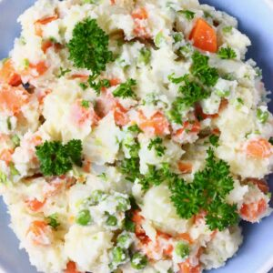 Potato salad with carrots, green peas and mayonnaise in a blue bowl