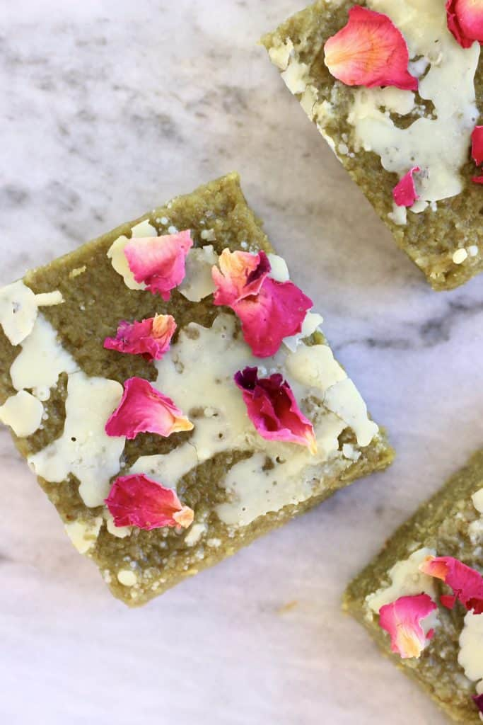 Three matcha brownies drizzled with white chocolate and decorated with rose petals