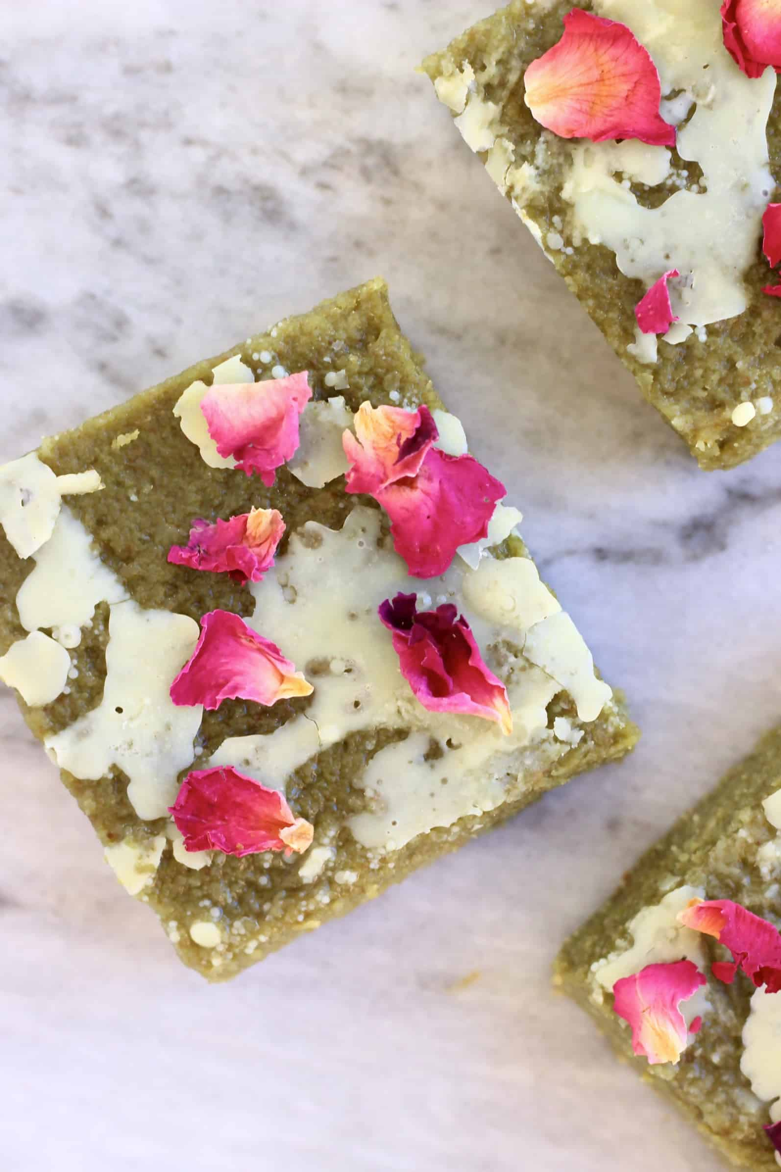 Three gluten-free vegan matcha brownies drizzled with white chocolate and decorated with rose petals