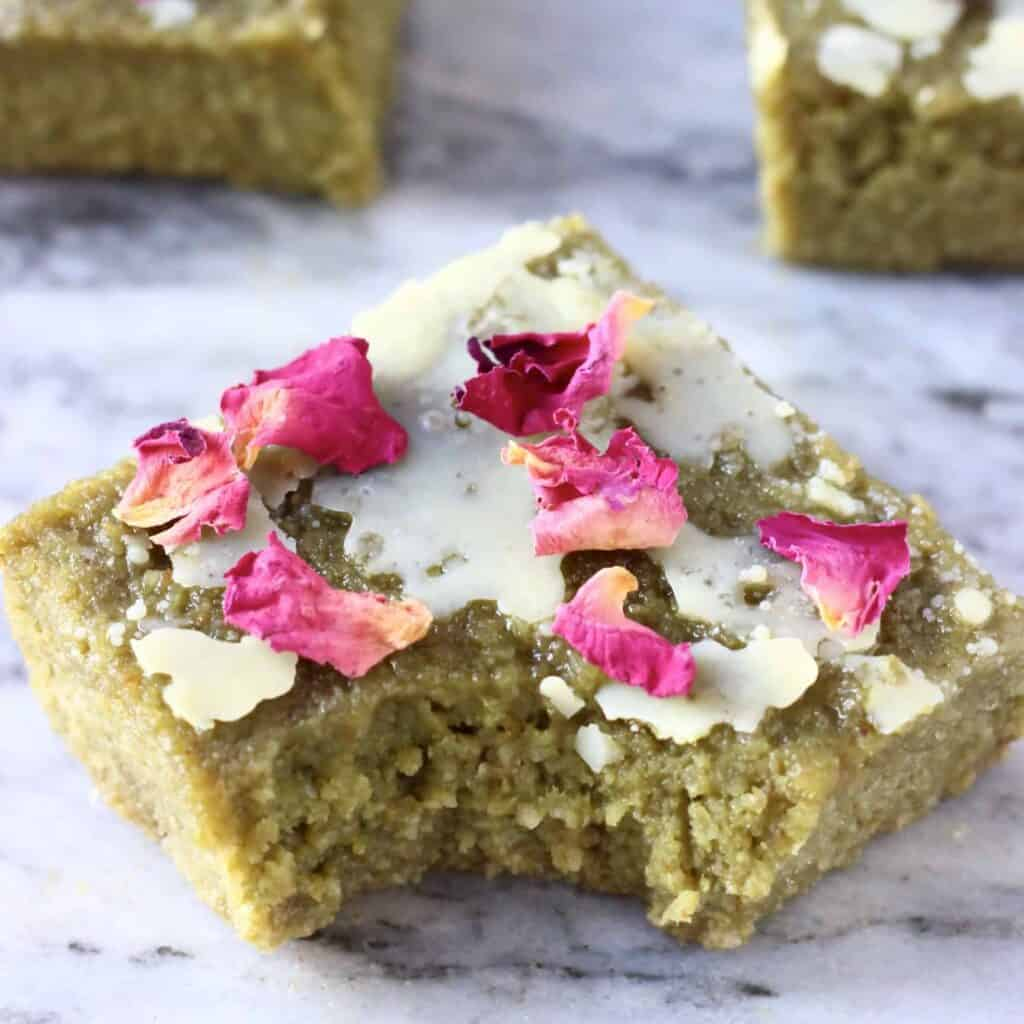 A matcha brownie topped with a white chocolate glaze and rose petals with a bite taken out of it