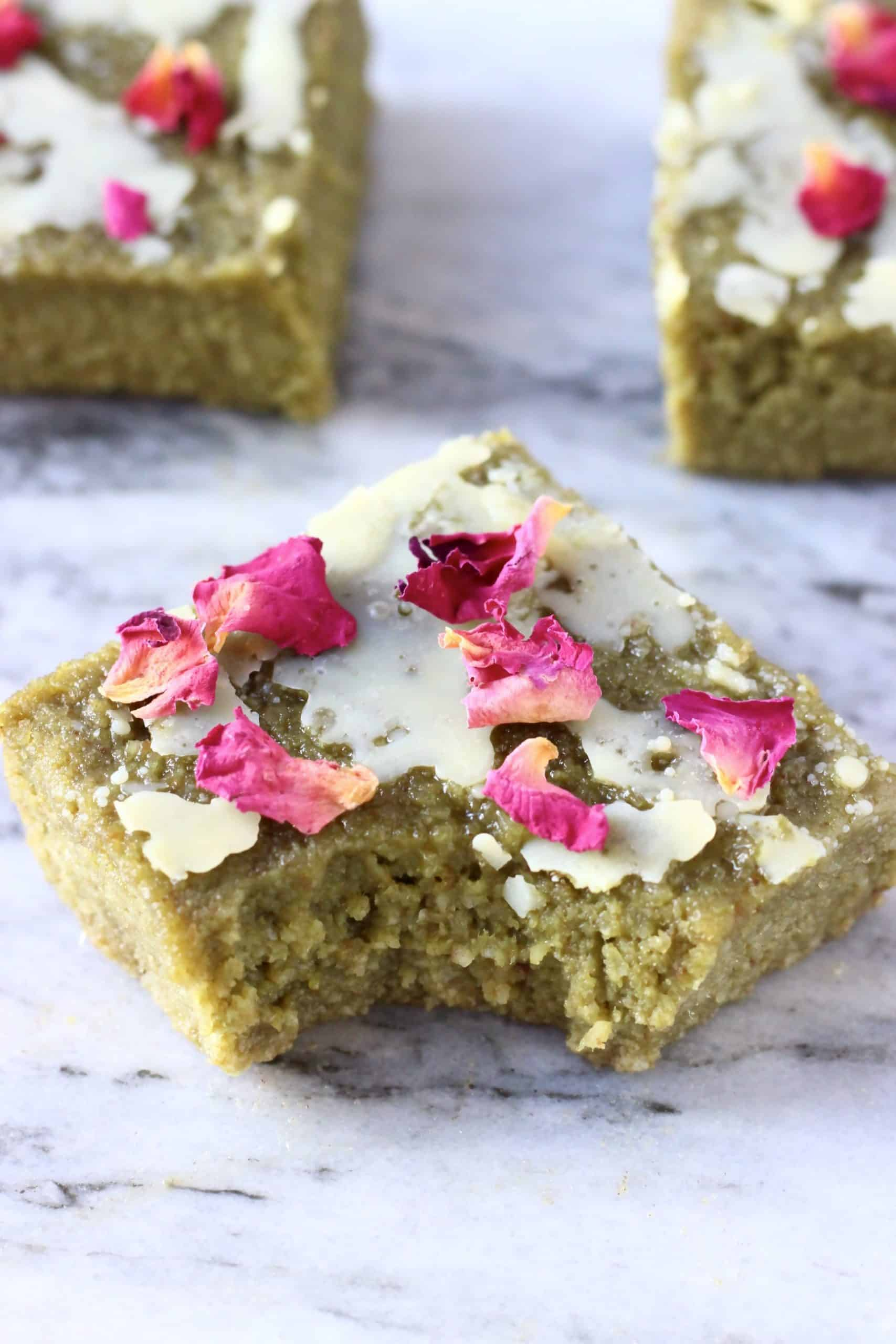 A gluten-free vegan matcha brownie topped with a white chocolate glaze and rose petals with a bite taken out of it