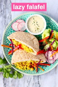 Two pittas filled with crushed chickpeas and salad on a green plate with a small white bowl of tahini sauce against a marble background