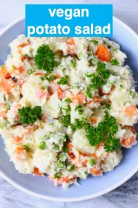 Potato salad with carrots, green peas and mayonnaise in a blue bowl against a marble background