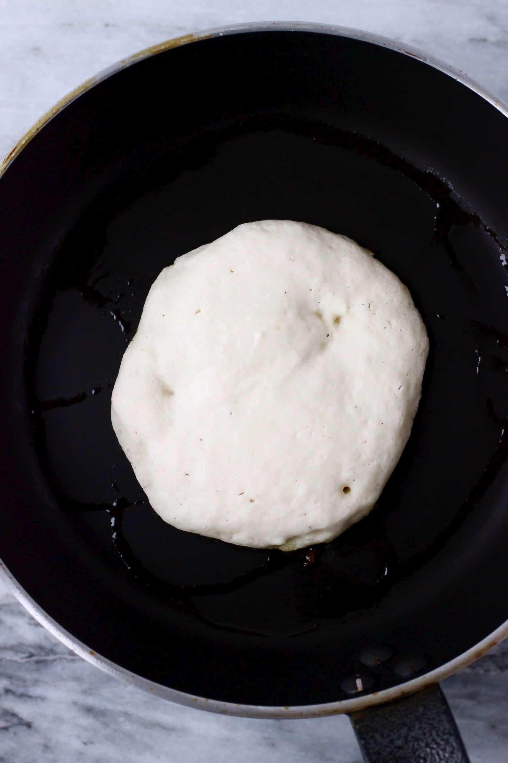 A white gluten-free vegan pancake being cooked in a black frying pan