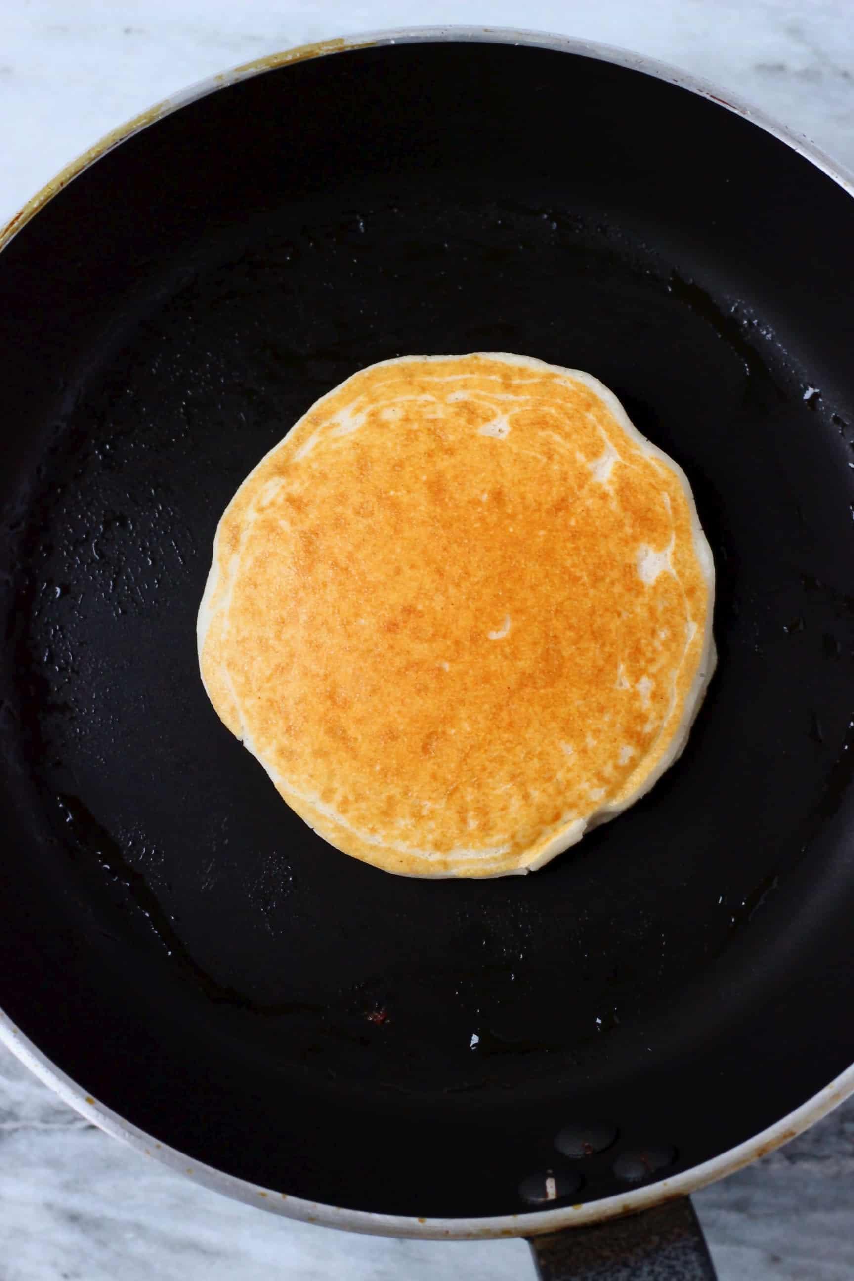 A golden brown gluten-free vegan pancake being cooked in a black frying pan