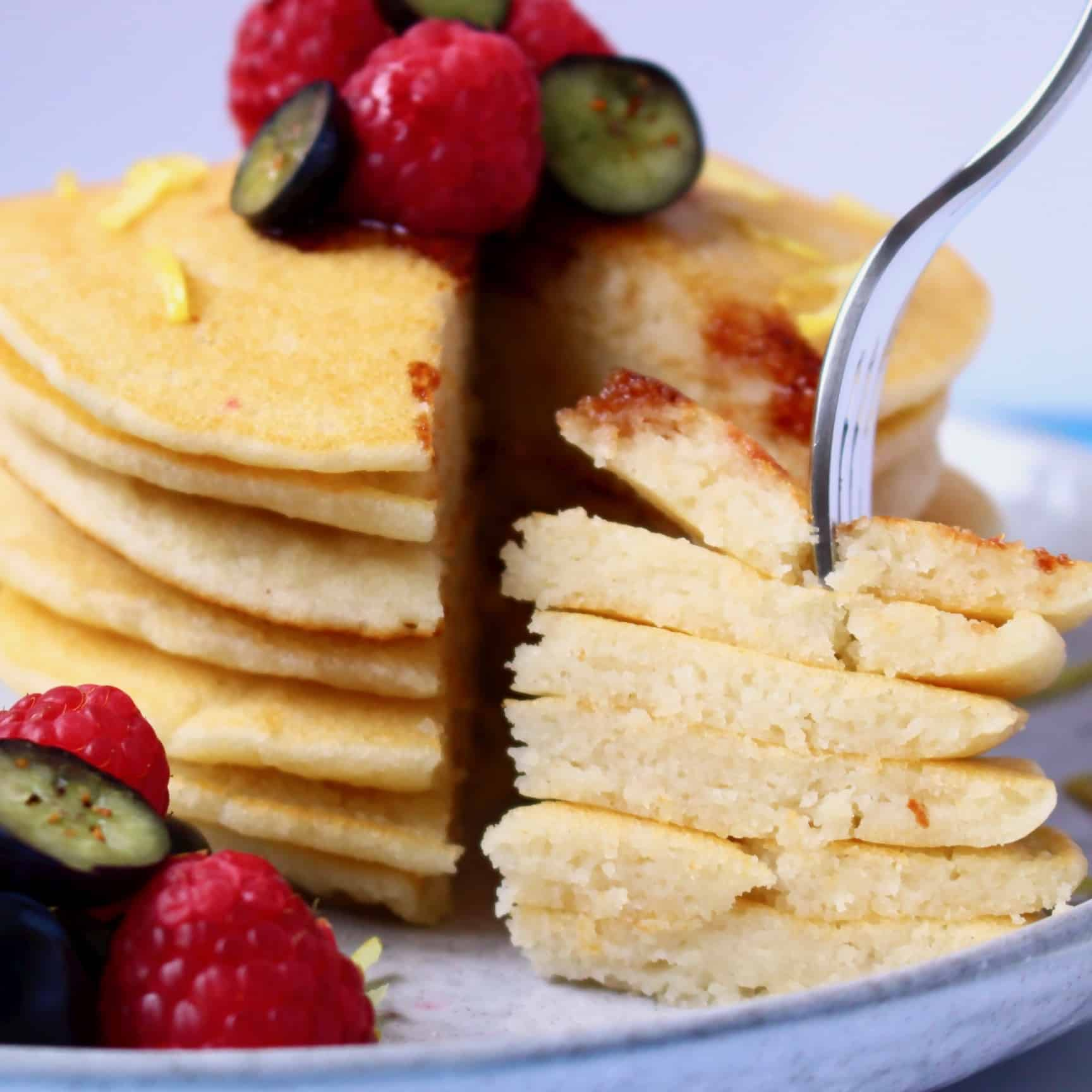 A stack of gluten-free vegan pancakes with a fork sticking into a slice of them