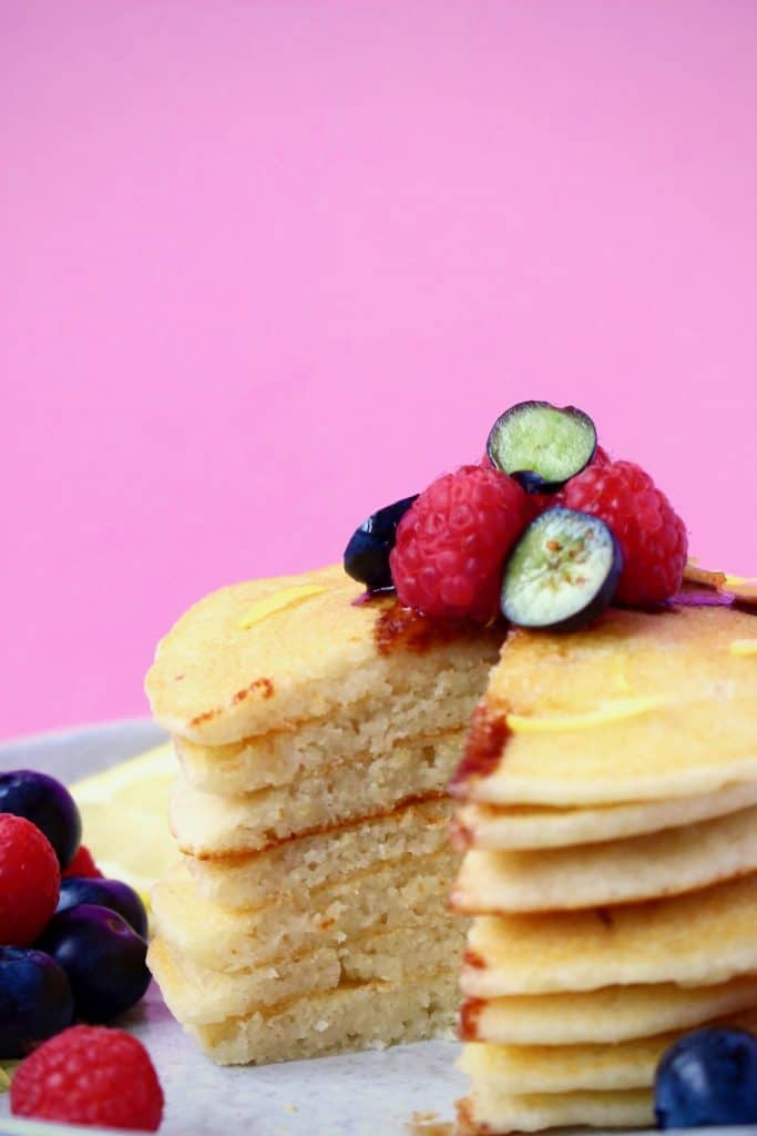 A stack of pancakes topped with fresh berries against a pink background