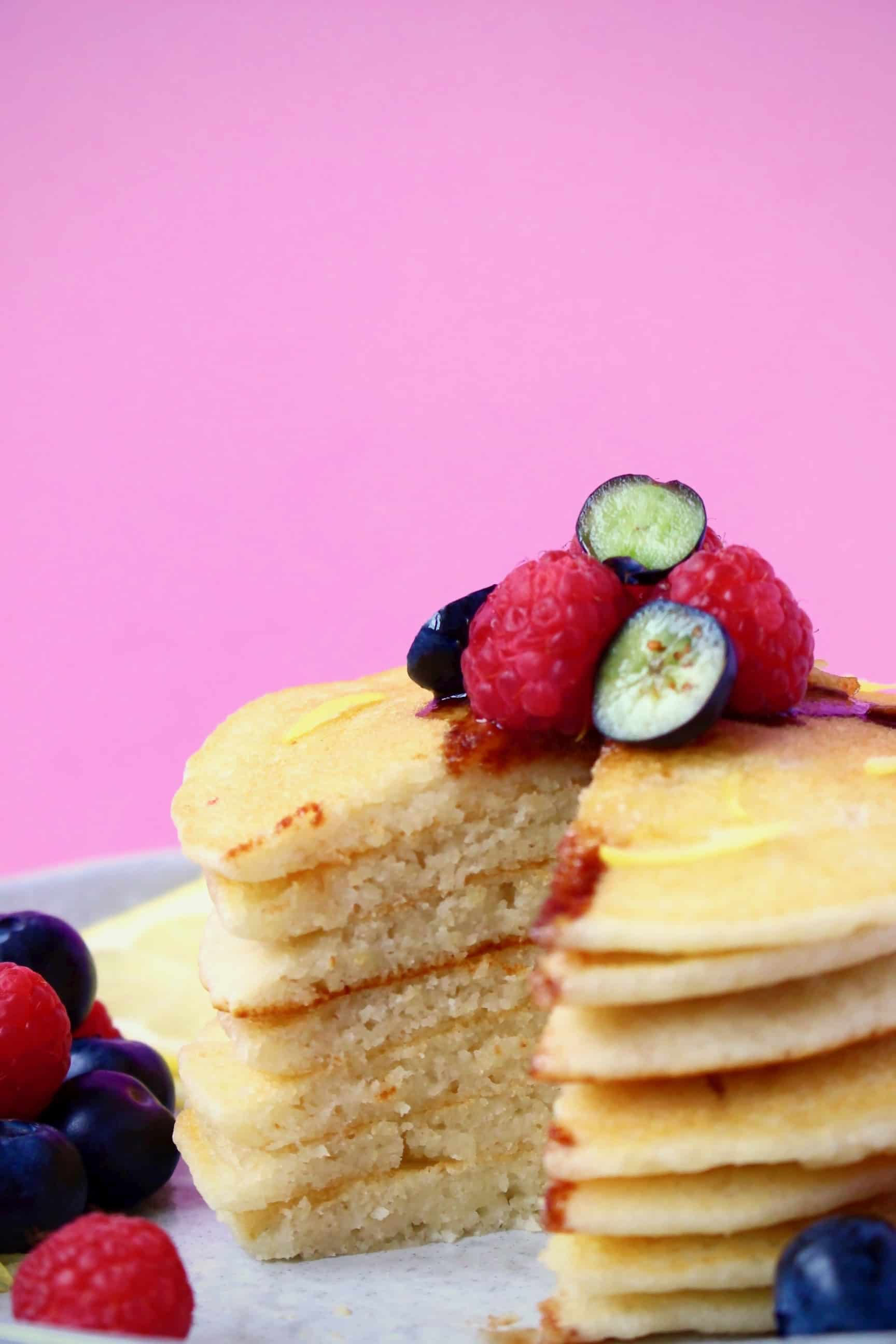 A stack of gluten-free vegan pancakes topped with fresh berries