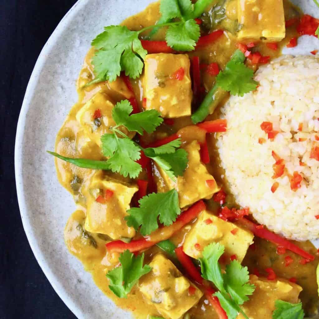 Photo of tofu cubes in a yellow curry sauce with green beans and red peppers on a grey plate alongside a mound of brown rice