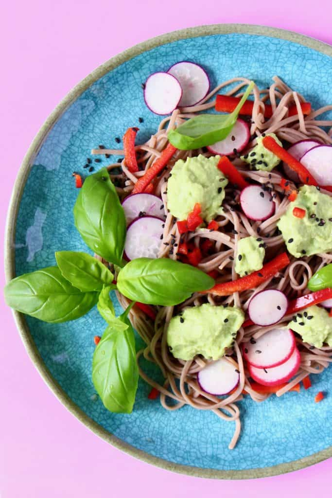 Soba noodles with edamame pesto, sliced radishes, red pepper matchsticks and basil on a blue plate against a pink background