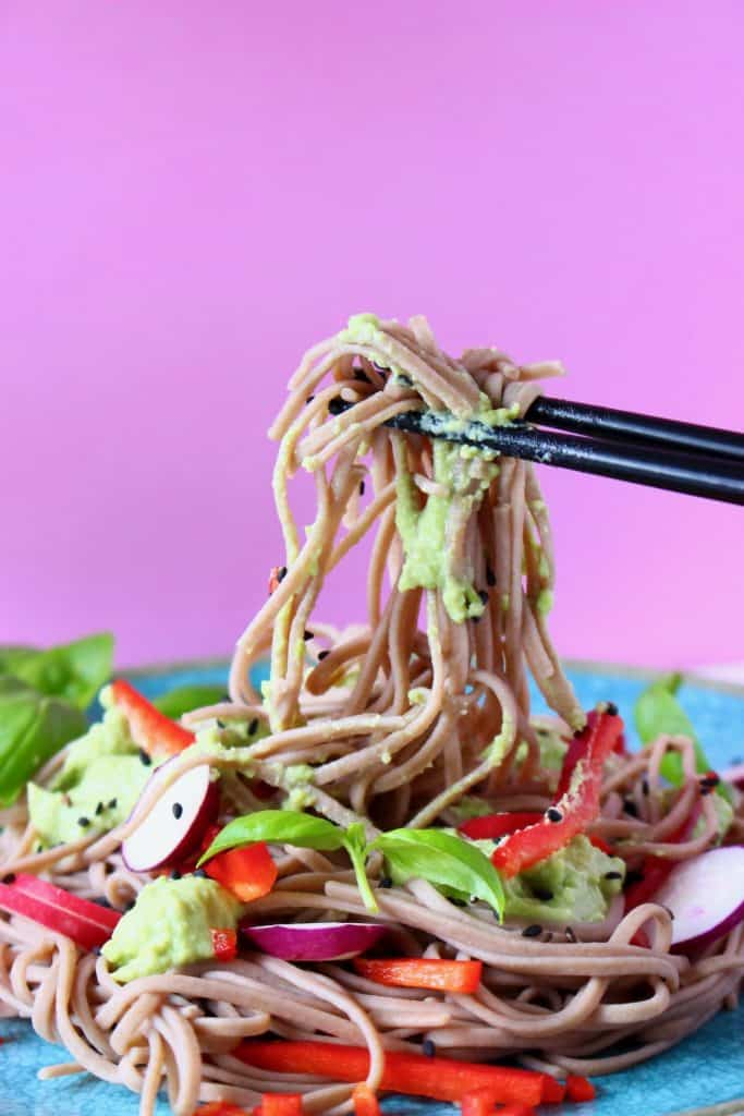 Soba noodles with edamame pesto, sliced radishes and red pepper matchsticks on a blue plate against a pink background with a pair of black chopsticks lifting up a mouthful
