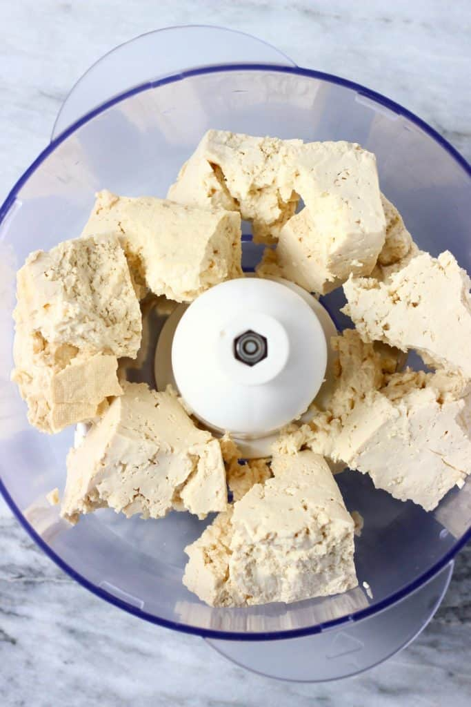 Broken up pieces of tofu in a food processor against a marble background