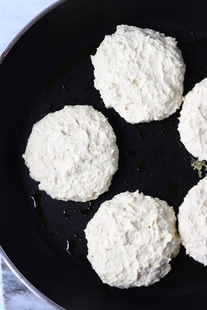 Five tofu burgers being fried in a black frying pan