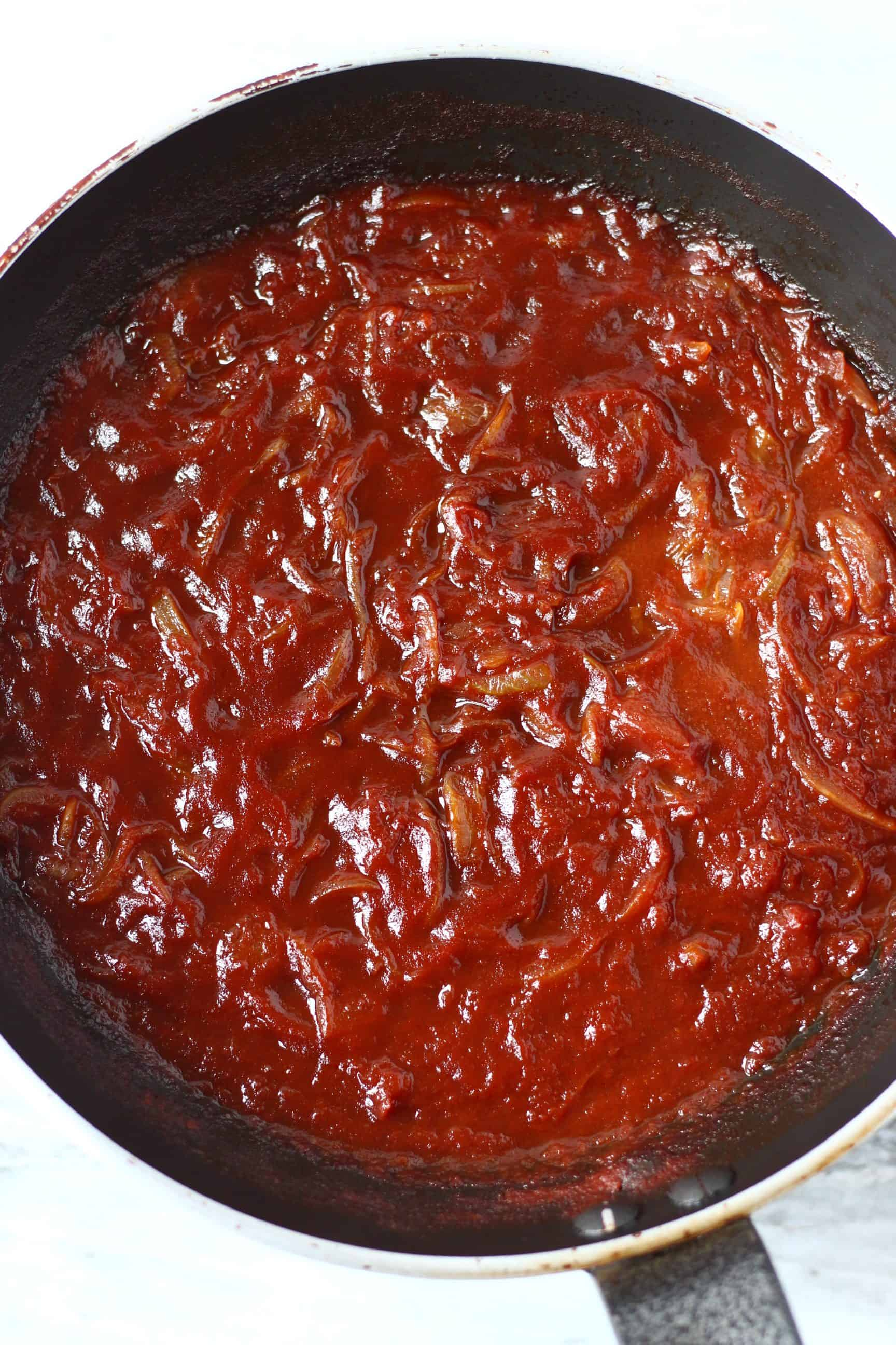 Onions with tomato sauce in a black frying pan against a marble background