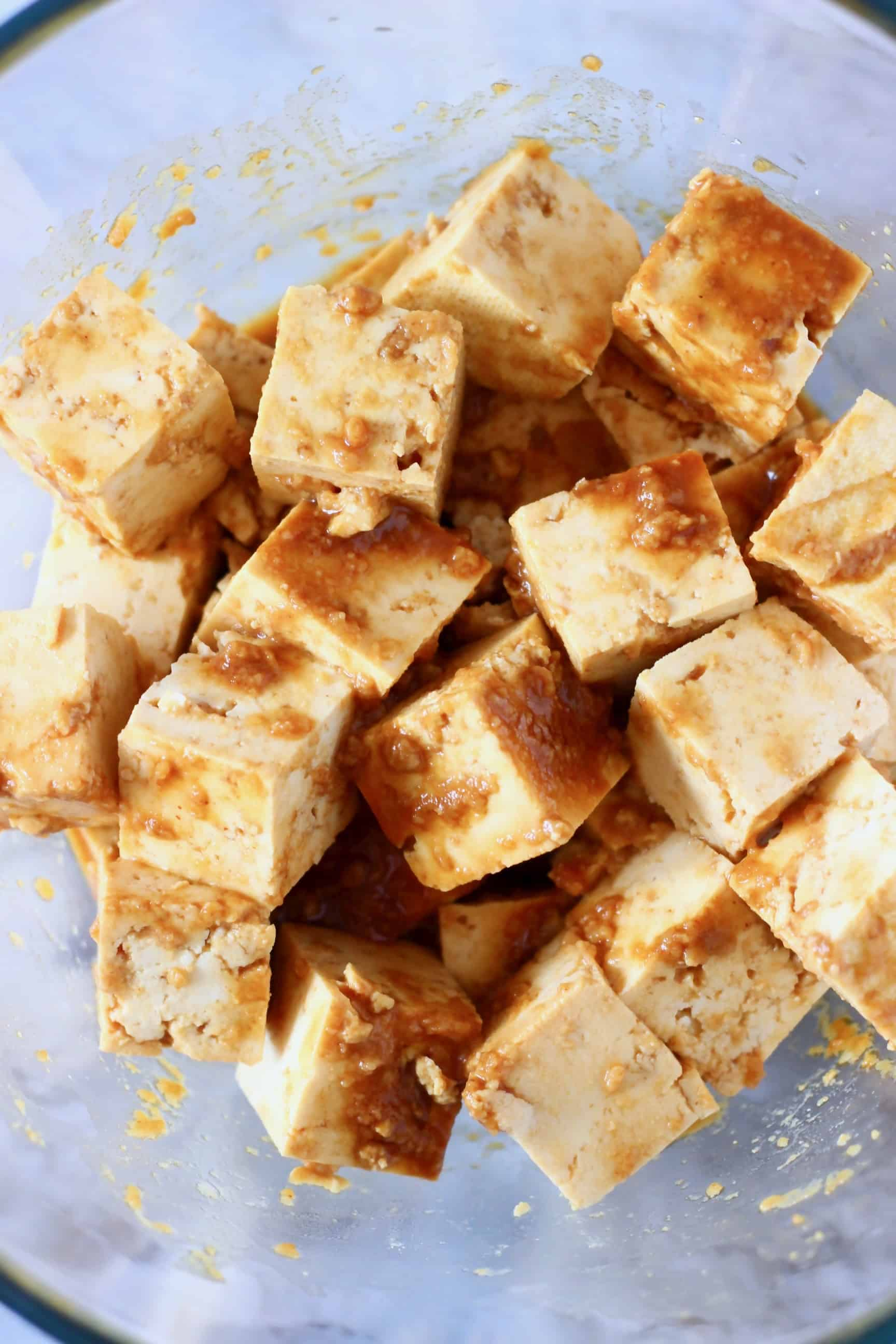Cubes of tofu marinating in a peanut sauce in a glass bowl