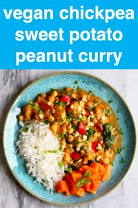 Chickpea and sweet potato curry and white rice on a blue plate against a marble background