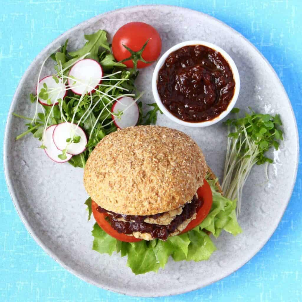 A burger on a grey plate with salad and a white pot of brown sauce against a bright blue background