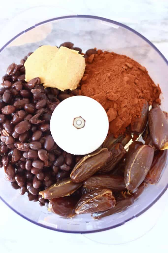 Photo of black beans, cocoa powder, dates and almond butter in a food processor taken from above