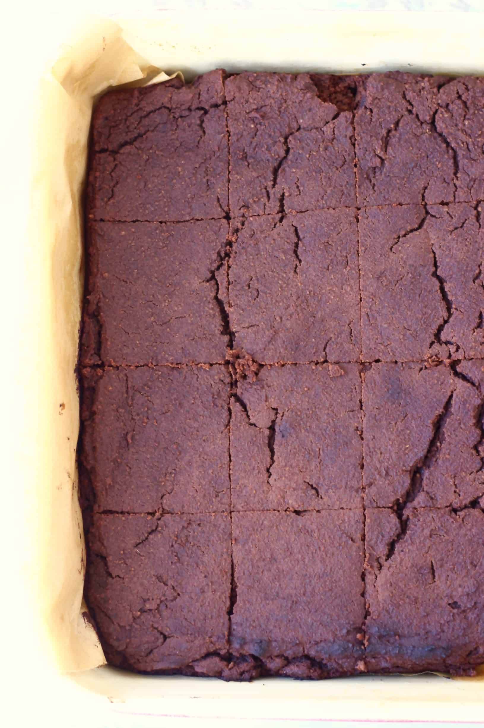 Vegan black bean brownies cut into squares in a square baking tin lined with baking paper