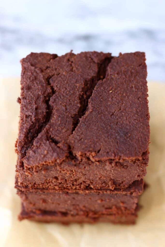 Photo of three chocolate brownies stacked on top of each other on a sheet of brown baking paper with a marble background