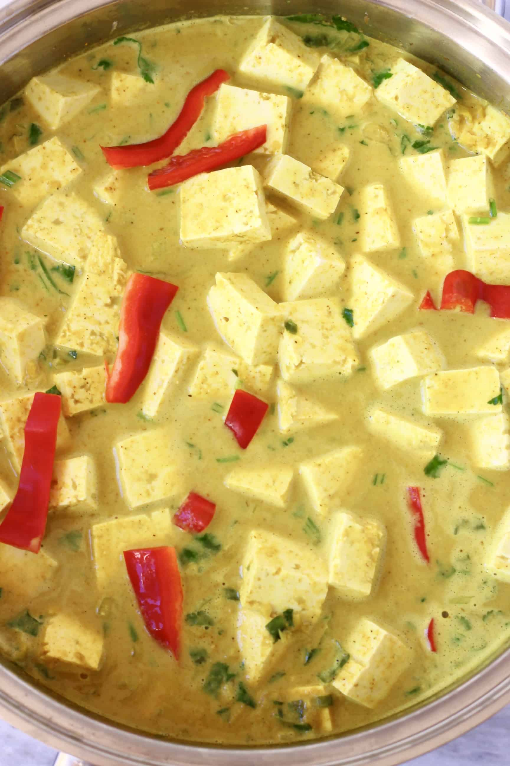 Cubes of tofu and strips of red pepper in a yellow curry sauce in a silver pan