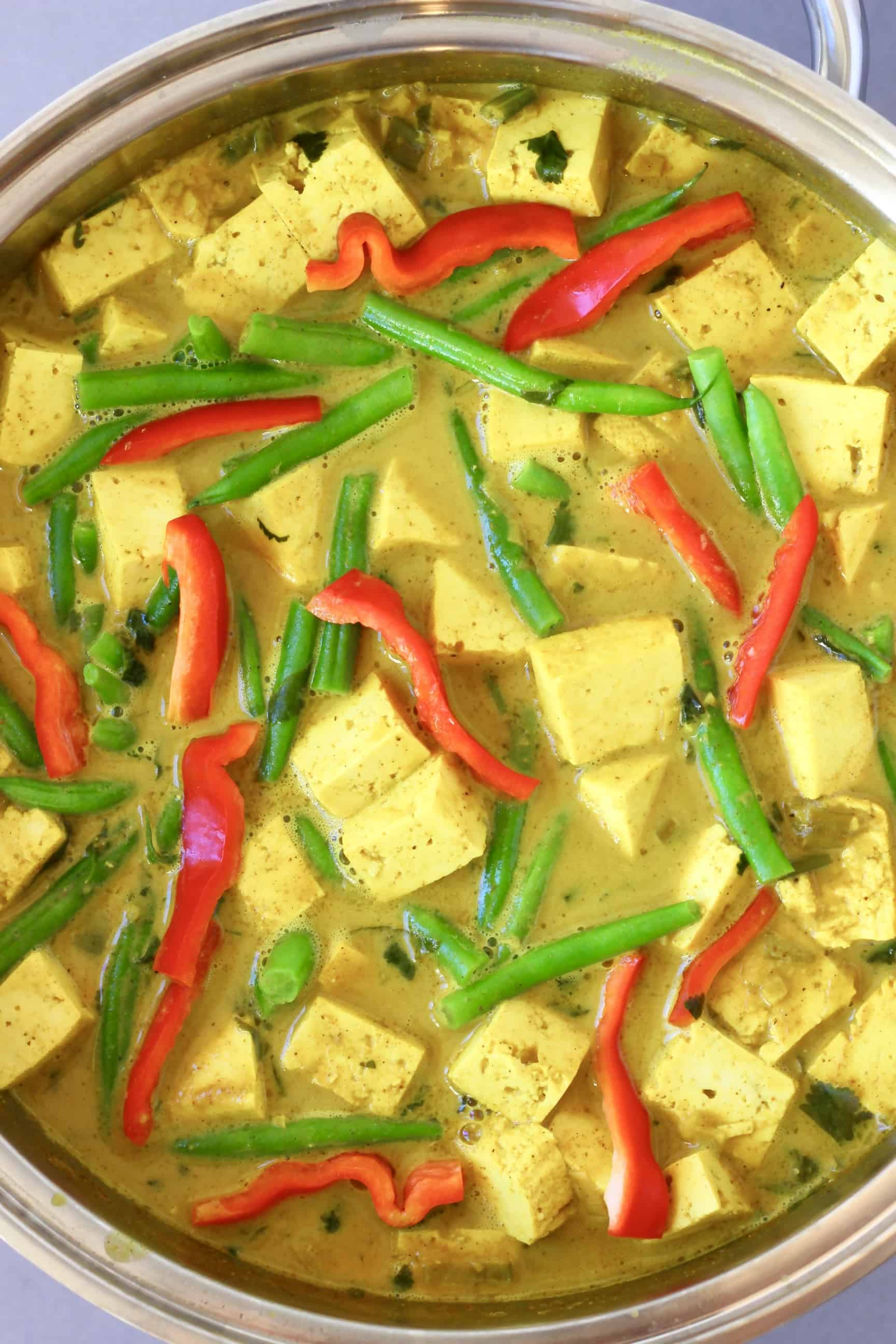 Cubes of tofu, green beans and strips of red pepper in a yellow curry sauce in a silver pan