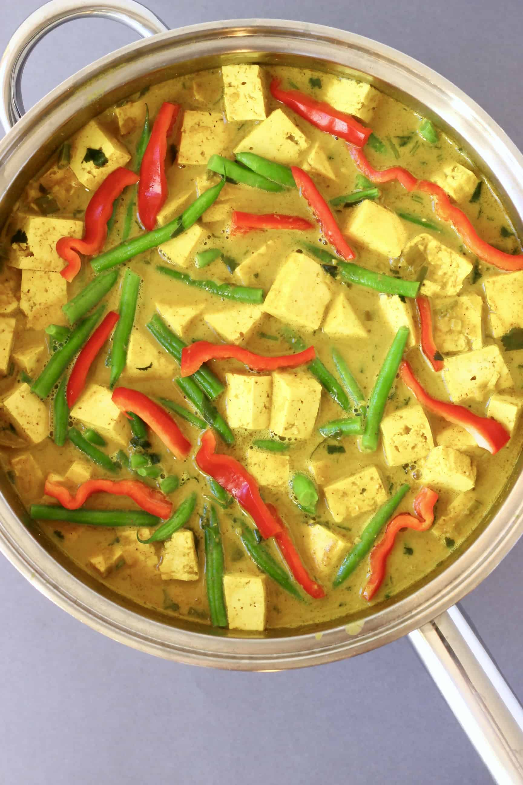 Peanut tofu satay curry with tofu, green beans and red pepper in a yellow curry sauce in a pan