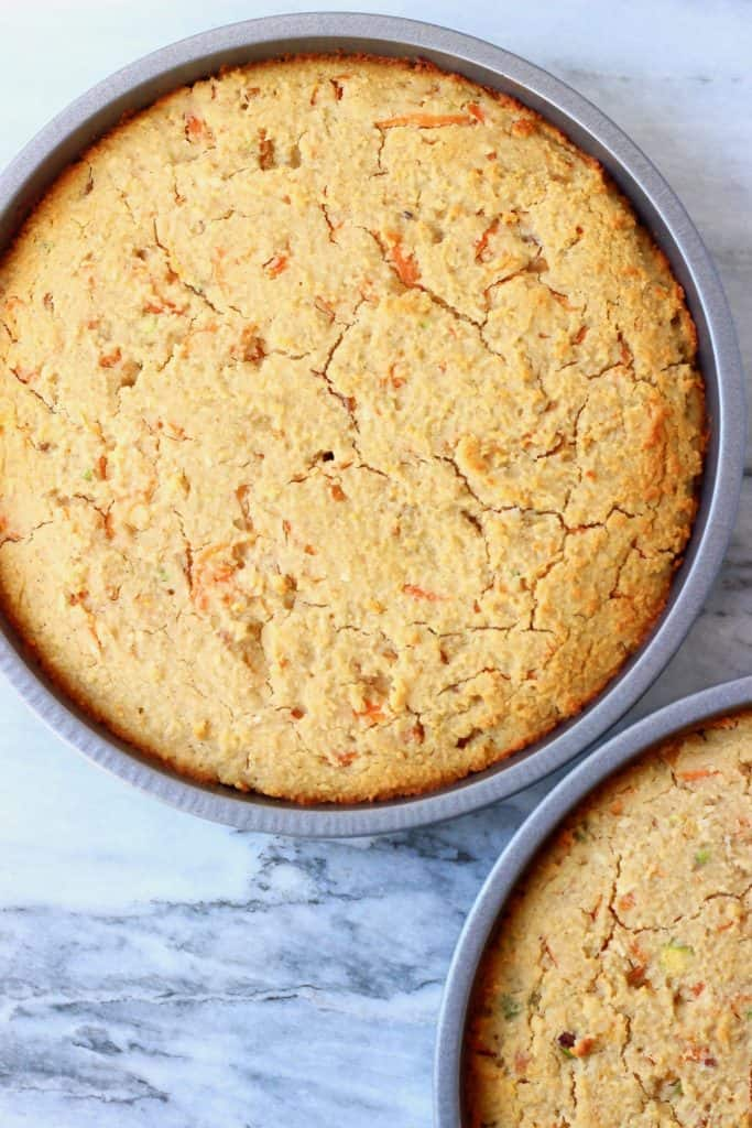 Carrot cake sponges in two silver baking tins against a marble background