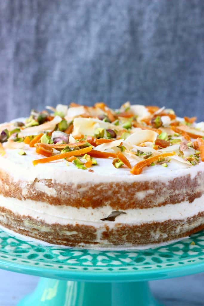 A carrot cake with white frosting decorated with dried mango, chopped pistachios and coconut flakes on a green cake stand against a grey background