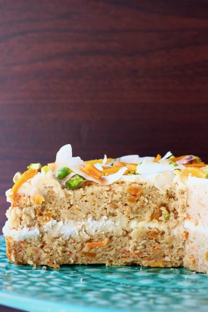 A carrot cake sponge cake with white frosting decorated with dried mango, chopped pistachios and coconut flakes on a green cake stand against a dark brown background
