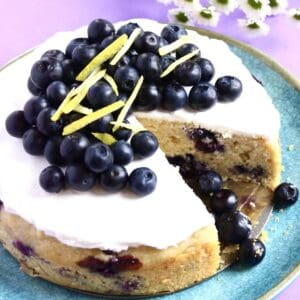 A gluten-free vegan lemon blueberry cake topped with cream and blueberries with a slice cut out of it