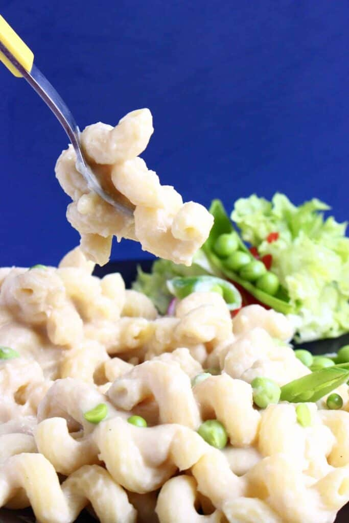 Photo of mac and cheese with green peas with a silver fork lifting up a mouthful against a dark blue background