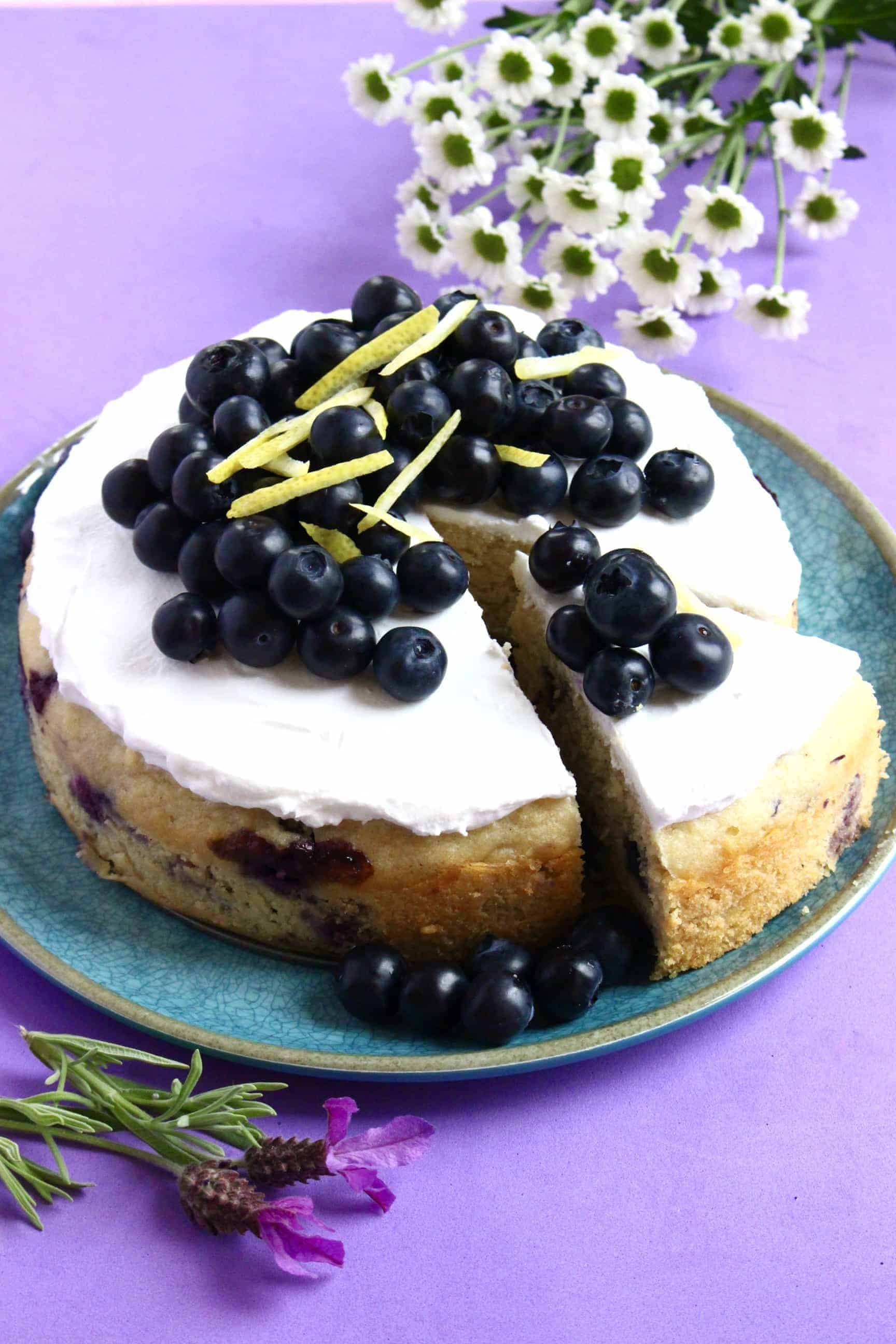 Gluten-free vegan lemon blueberry cake topped with blueberries on a blue plate