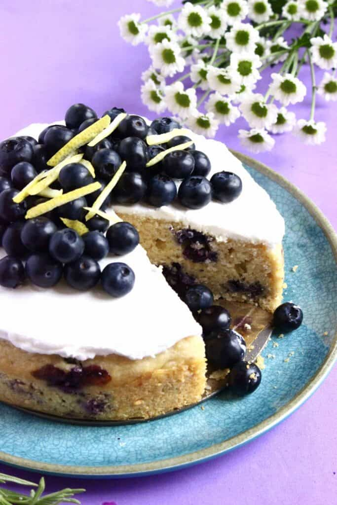 Photo of a blueberry sponge cake topped with white frosting and blueberries on a blue plate with a purple background and a slice taken out of the cake