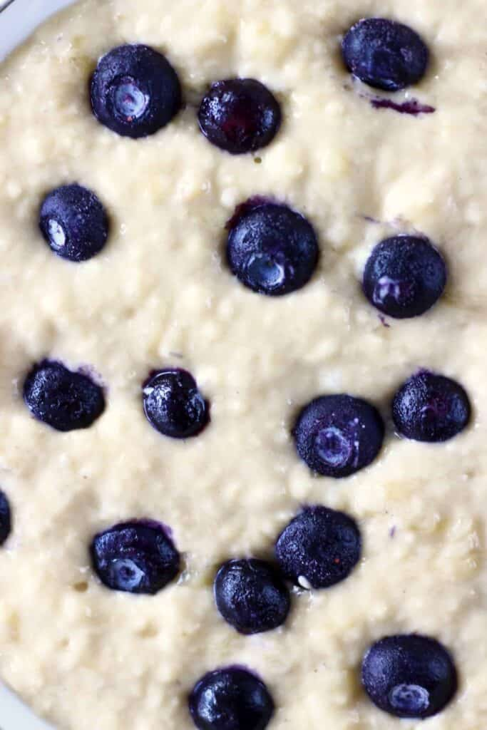 A bowl of sponge cake batter in a bowl with blueberries taken from above