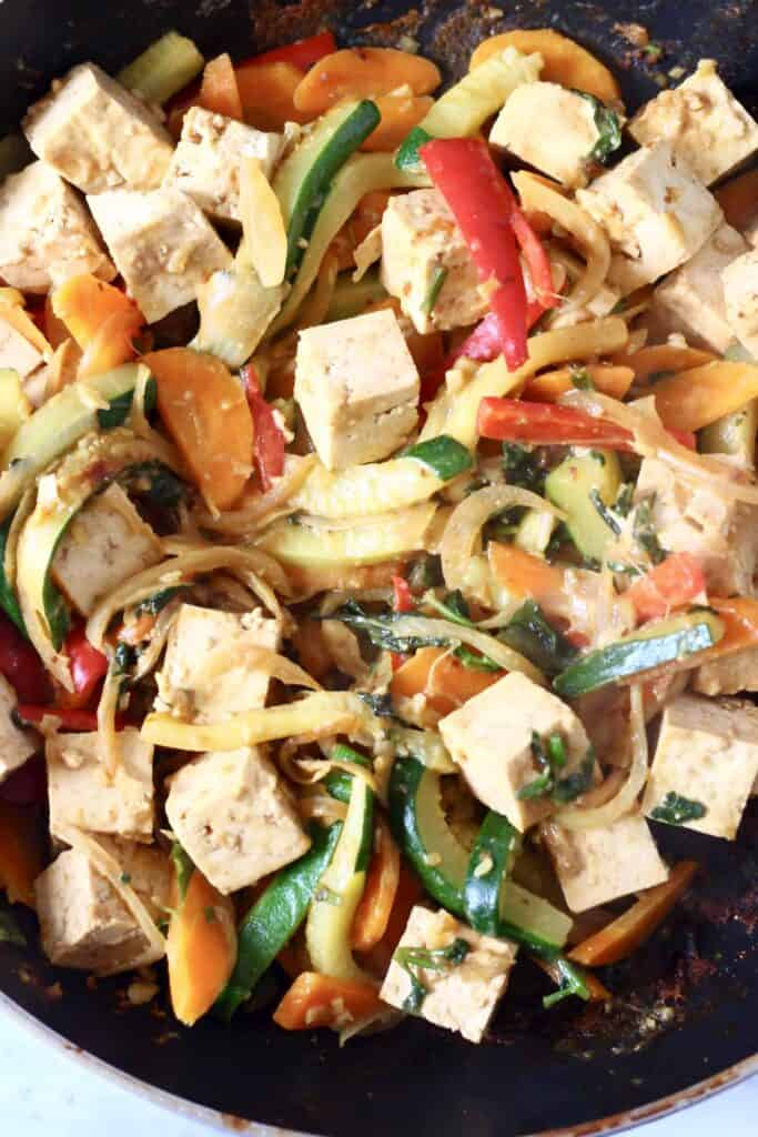 Photo of chopped vegetables and tofu cubes in a black frying pan