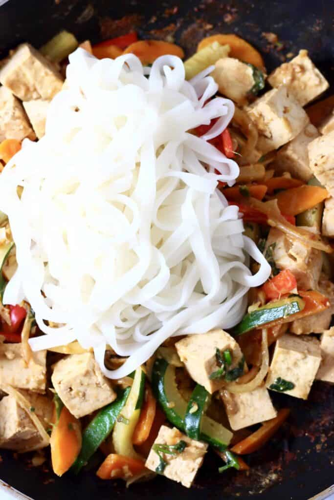Photo of chopped vegetables, tofu cubes and rice noodles in a black frying pan