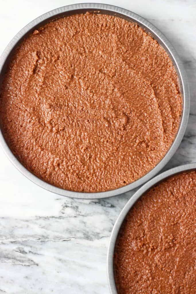 Two sponge cake tins filled with raw chocolate cake batter against a marble background