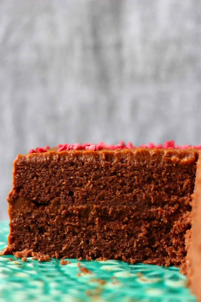 A sliced chocolate cake sandwiched with chocolate frosting and covered in chocolate frosting sprinkled with pink freeze-dried raspberries on a green cake stand against a grey background