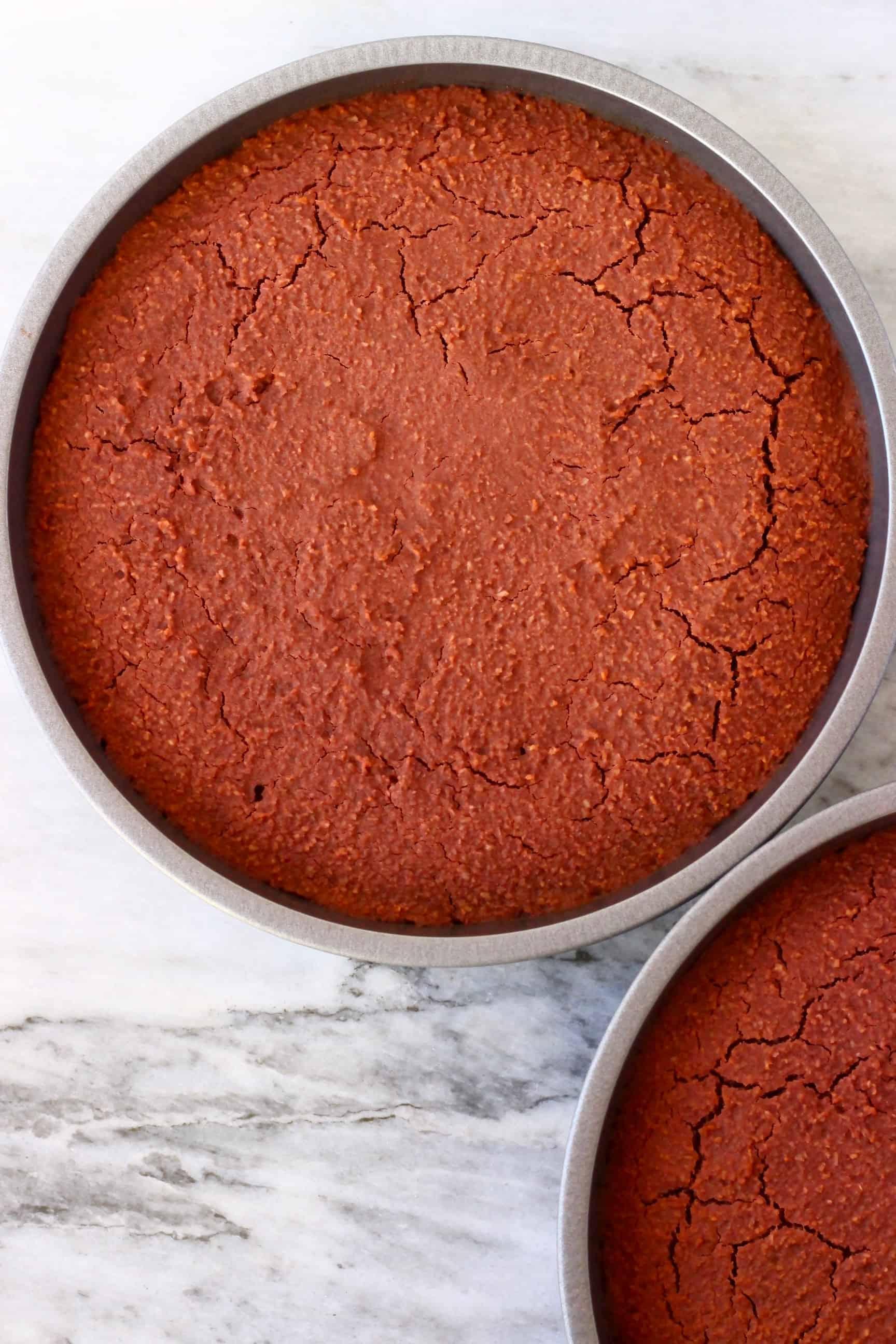 Two gluten-free vegan red velvet cake sponges in circular baking tins