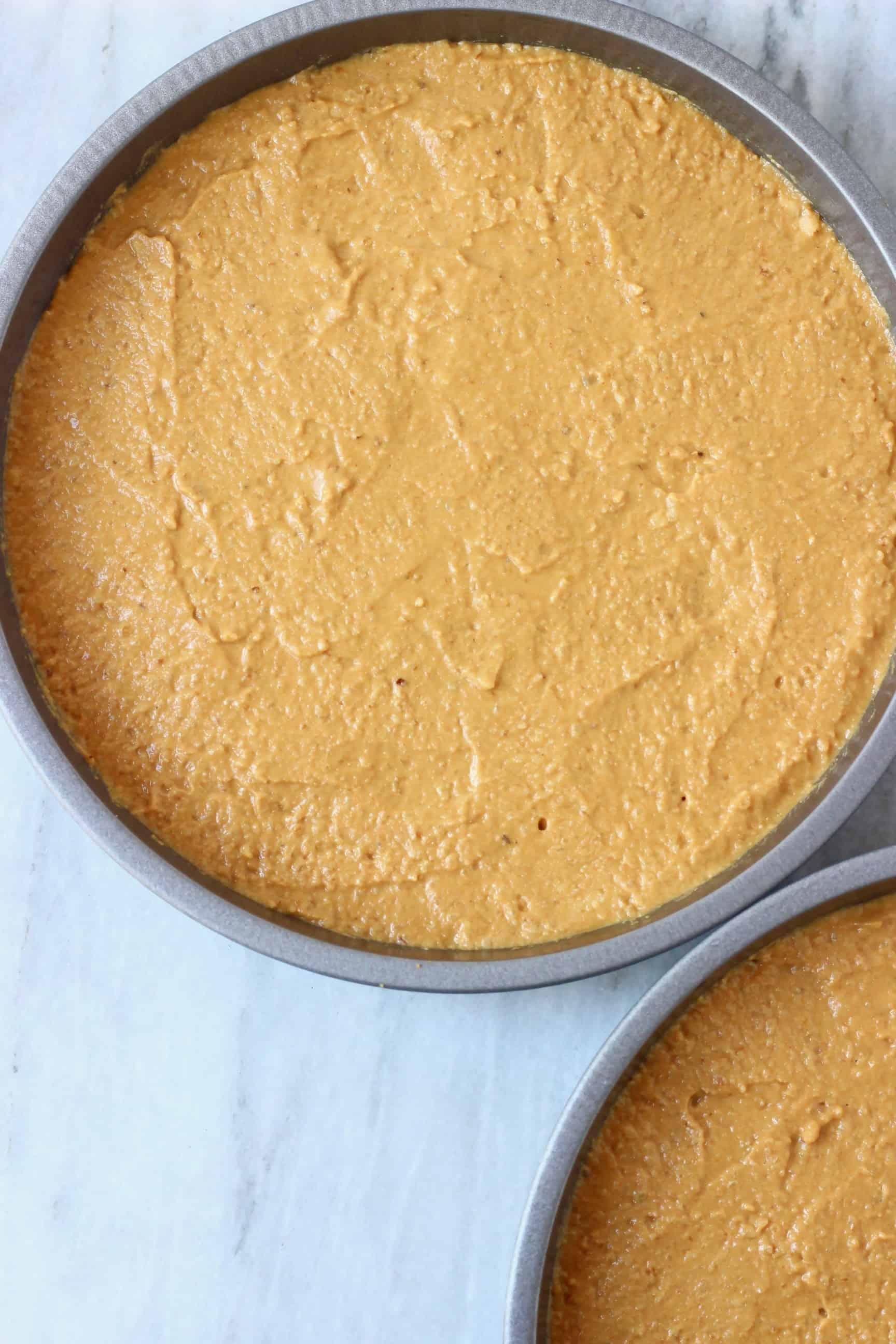 Raw gluten-free vegan coffee cake batter in two round baking tins