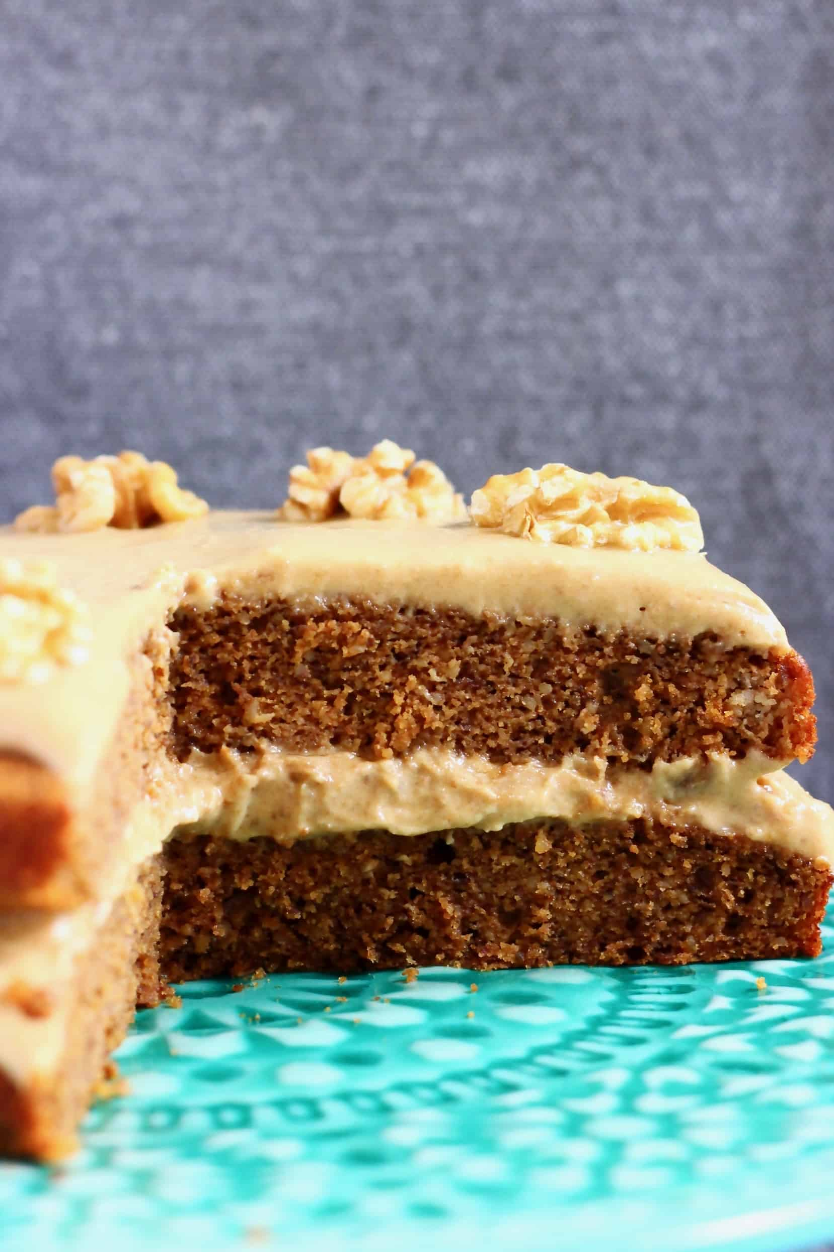 A sliced gluten-free vegan coffee cake with coffee frosting and walnuts on a cake stand