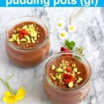 Photo of two chocolate pots topped with chopped pistachios and goji berries on a marble background decorated with flowers