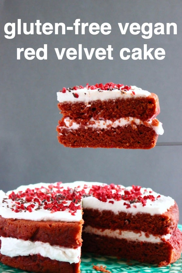 Red velvet cake with white creamy frosting sprinkled with freeze-dried raspberries with a slice being held up against a grey background