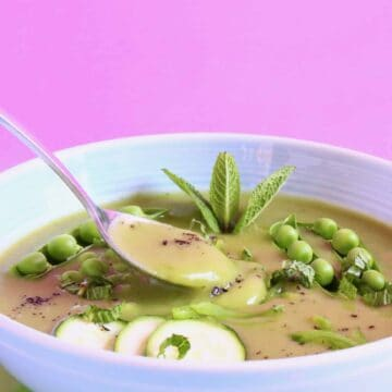 Green soup topped with green vegetables in a light blue bowl against a pink background with a silver spoon lifting up a mouthful